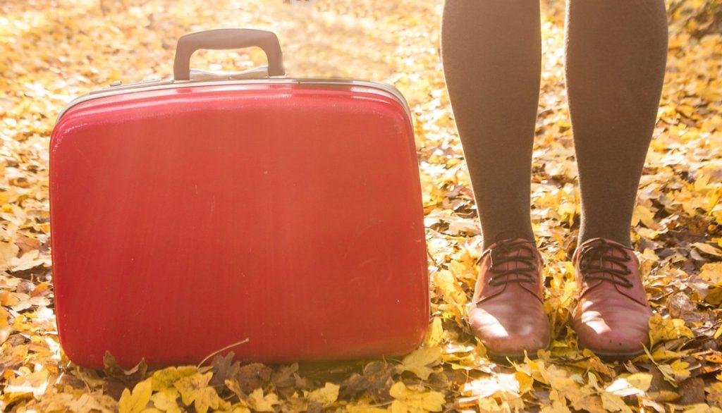 een rode koffer met de benen en schoenen van een vrouw